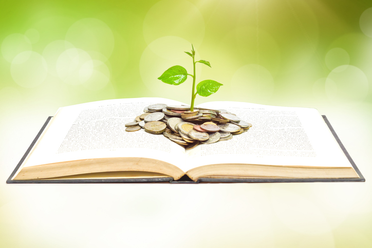 tree growing from book with coins