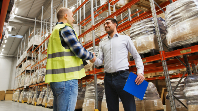 Warehouse employee and manager shaking hands