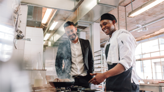Chef and manager smiling in restaurant kitchen