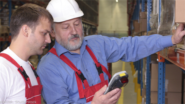 Older working training a younger worker in a warehouse