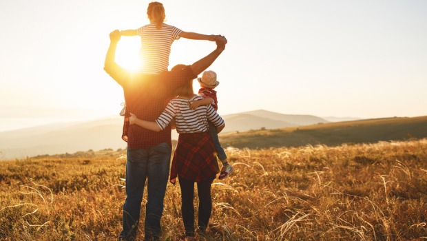 A family standing in a field at sunset.
