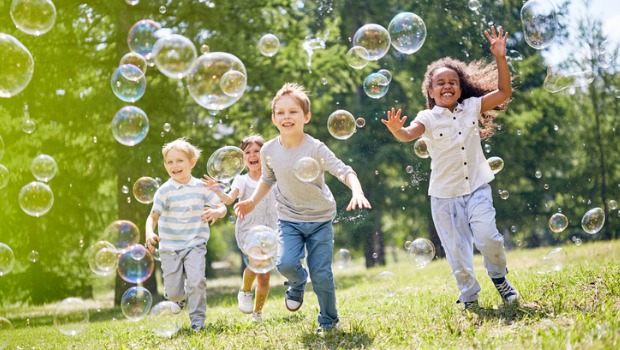 Children chasing bubbles in a park.