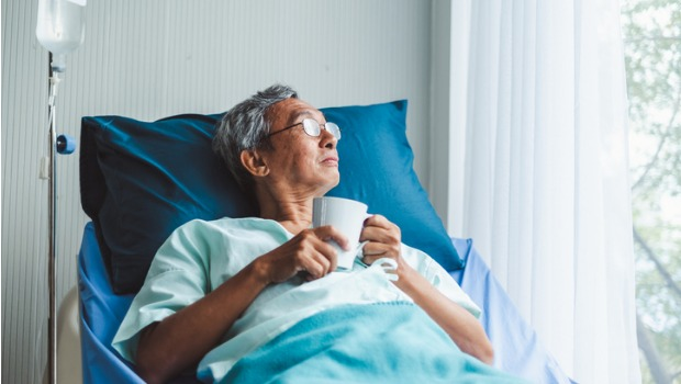 A man sits in a hospital bed looking out the window.