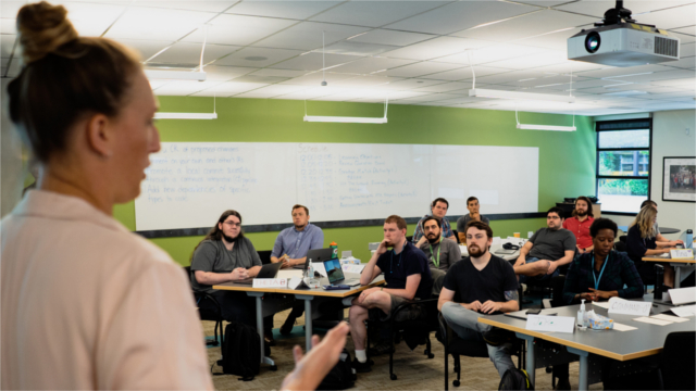 A woman stands at the front of a classroom as she speaks to around a dozen individuals who are seated across the room. Photo credit: Jordan Stead / Amazon