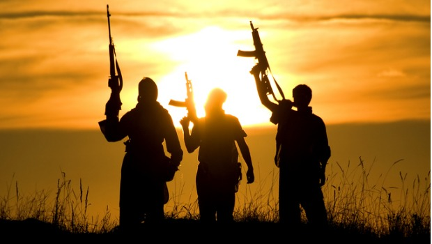 Soldiers standing against a sunset with their guns held in the air.