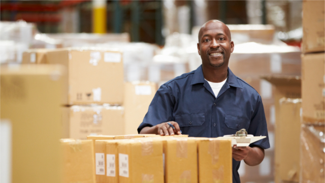 Smiling warehouse worker holding a clipboard near a stack of boxes