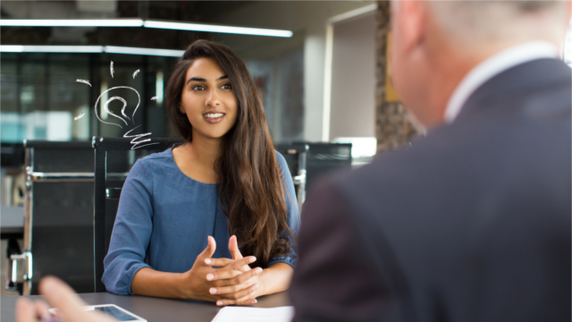 Young woman speaking with colleague at conference table
