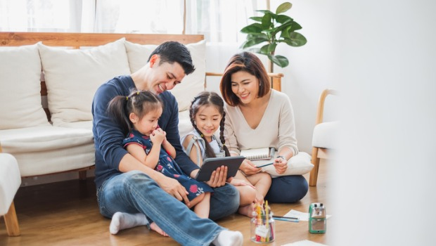 A family with two children sitting using a tablet together.