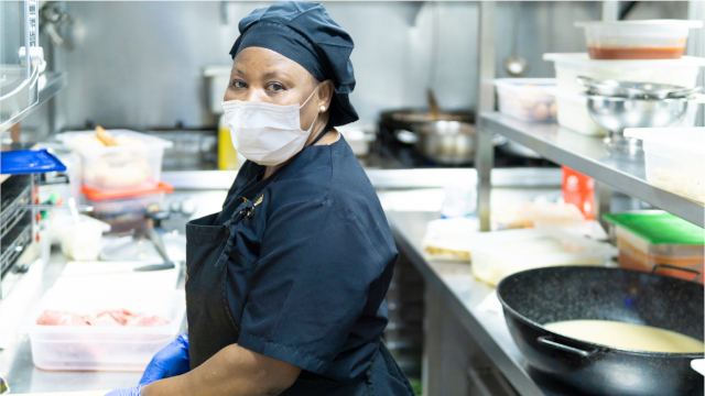 African American woman restaurant worker wearing a face mask in the kitchen